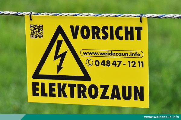 """Warnschild """"Vorsicht Elektrozaun"""" hängt im Leitermaterial."""